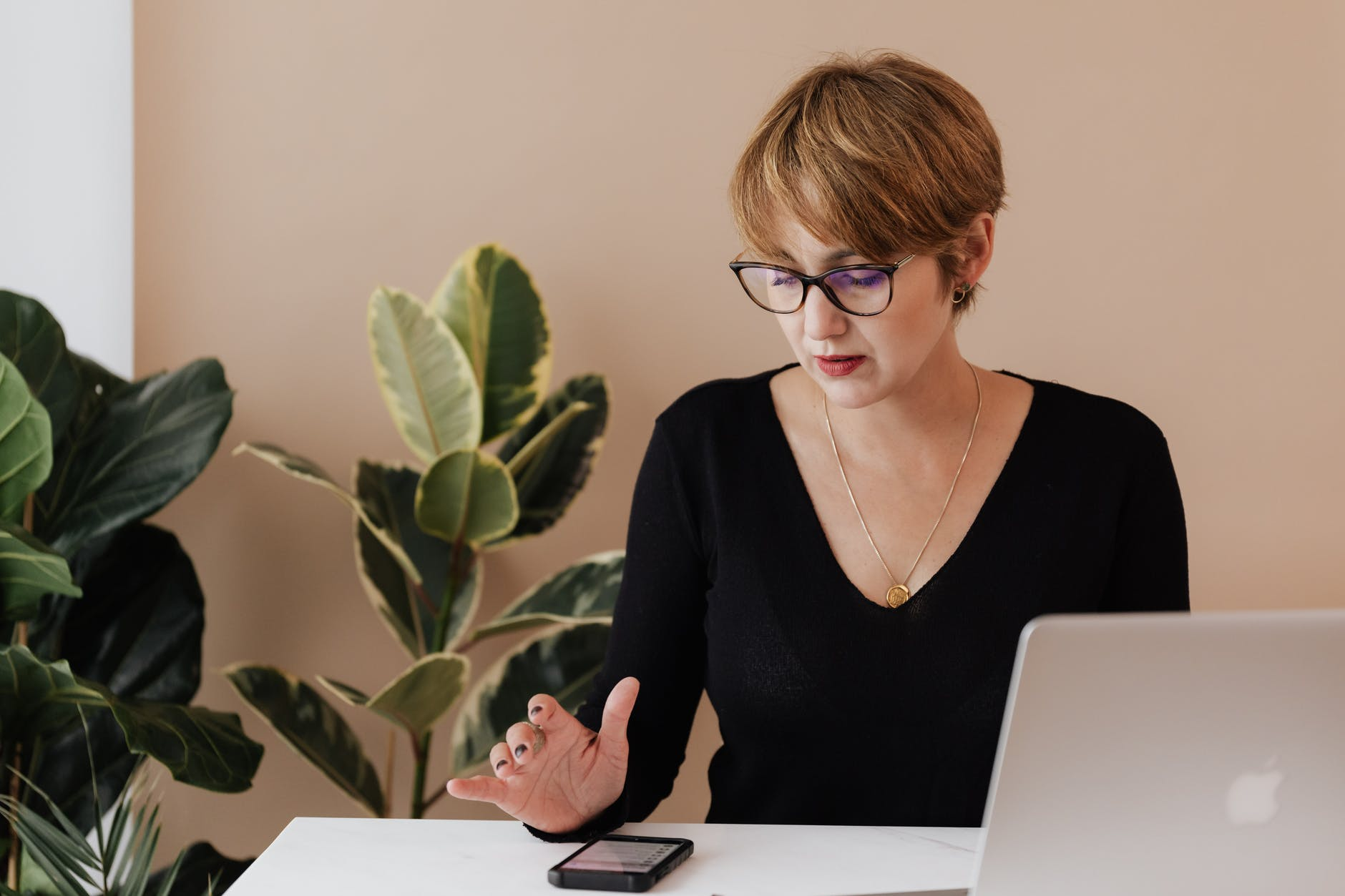 serious woman using mobile phone while working in office with laptop